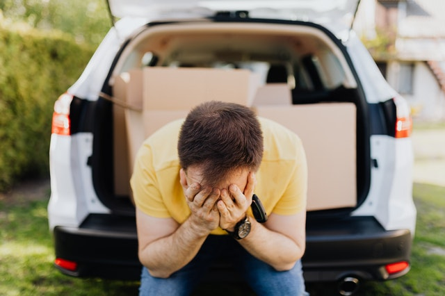 A man holding his head because he hasn't considered all the tips for choosing the best moving company for your family relocation.