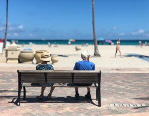 A senior couple sitting on a bench near a Florida beach