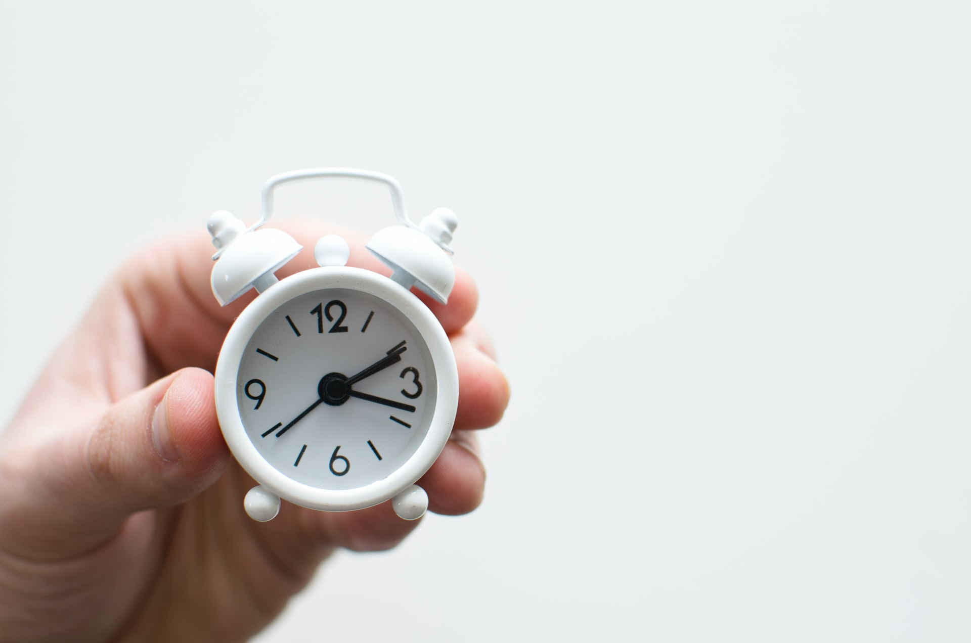 A person holding a small clock representing one of the most popular diets - intermittent fasting