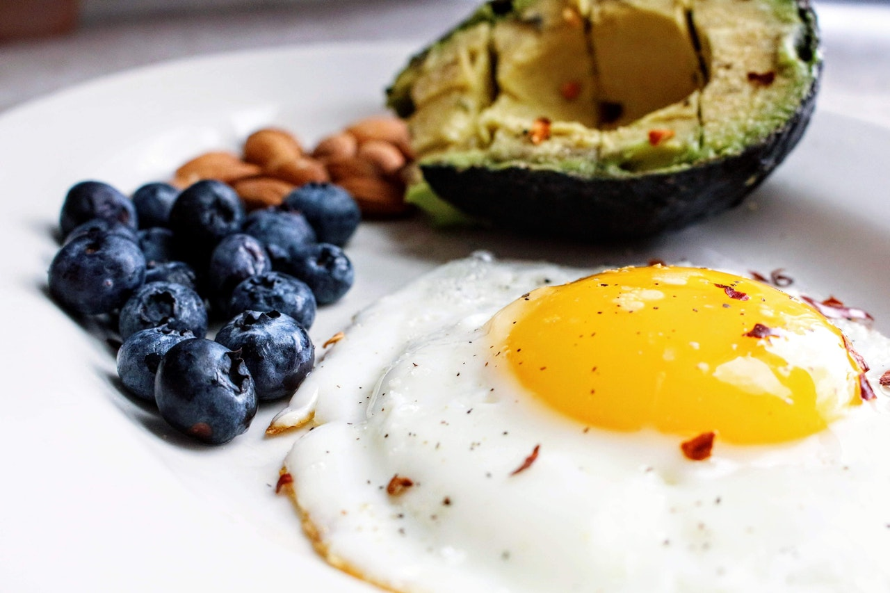 A plate of eggs, avocado, almonds, and blueberries