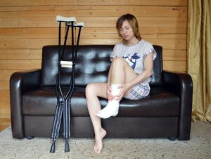A girl with an injured ankle sitting on a couch
