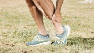 A person in blue sport's shoes holding their ankle