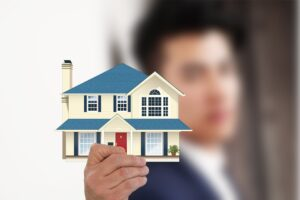 A real estate agent holding an illustration of a house